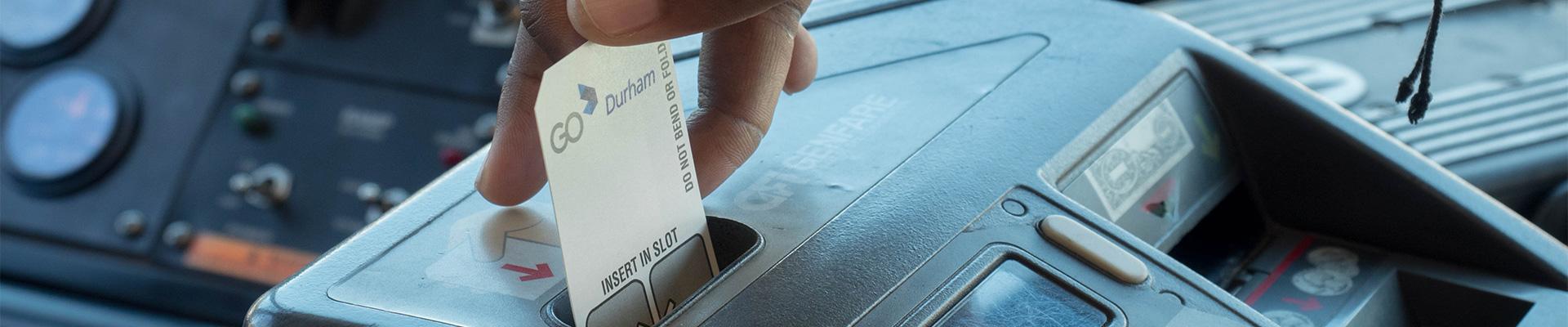 GoDurham Rider slides fare card though bus fare box